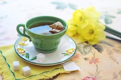 Vintage celadon green tea cup on white saucer with yellow and green flowers. Tea helps artists remember the beauty of every day things.