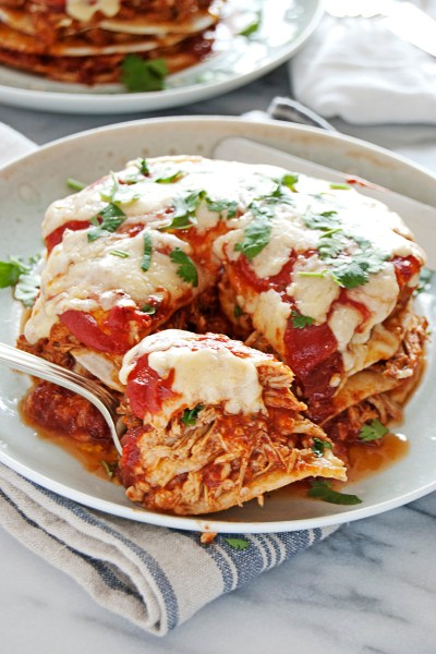 These mini crockpot chicken enchiladas feature slow cooked shredded chicken full of tasty Mexican flavors, a beautiful red sauce, and lots of cheese and cilantro!