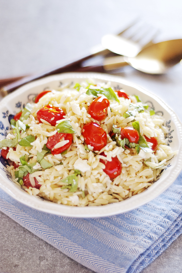 This 30 minute orzo pasta salad is the perfect side dish for your summer meals! It features burst cherry tomatoes, fresh basil, and feta cheese!