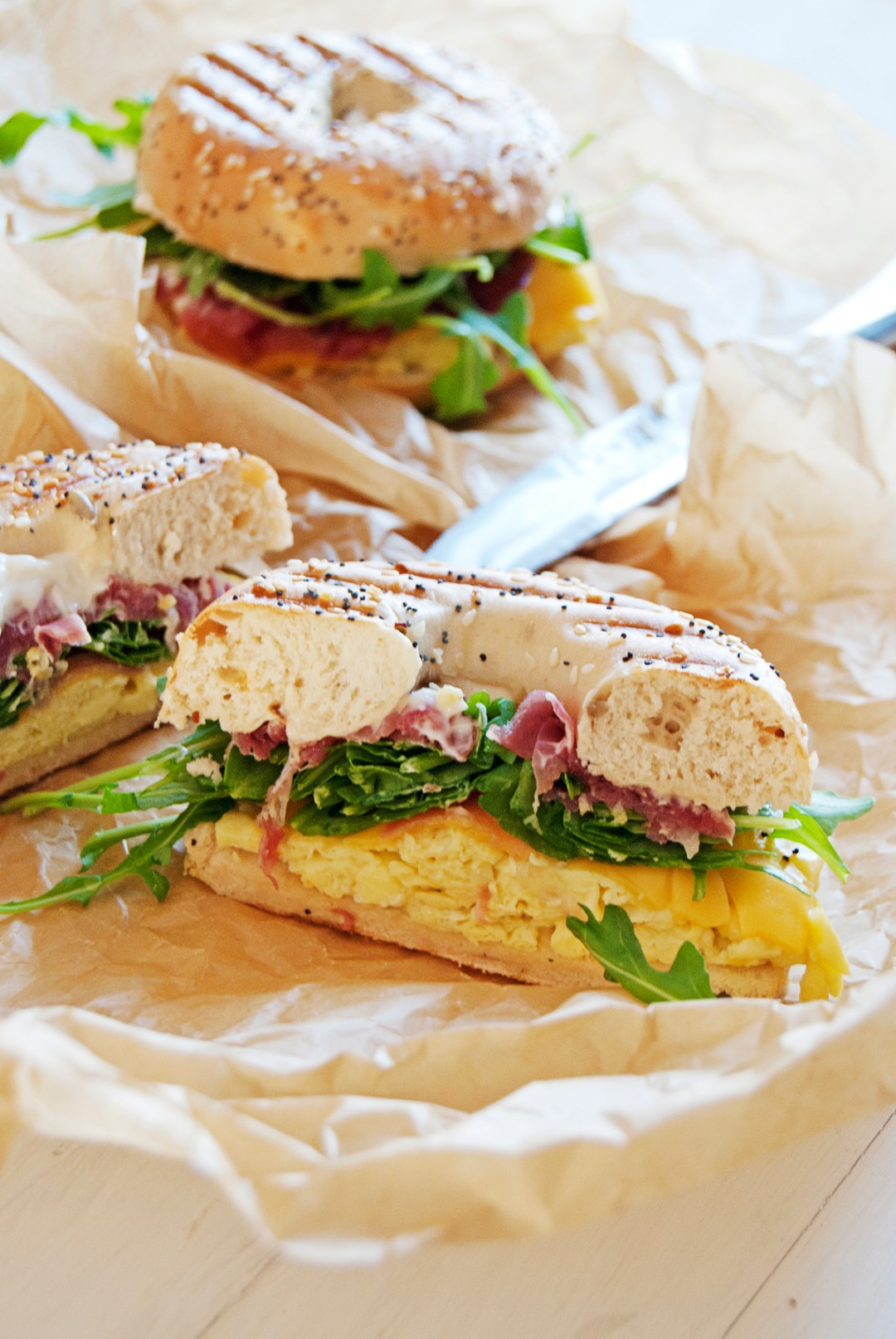 These breakfast bagel paninis are the perfect tasty brunch, featuring scrambled eggs, American cheese, arugula, prosciutto, and mayo.