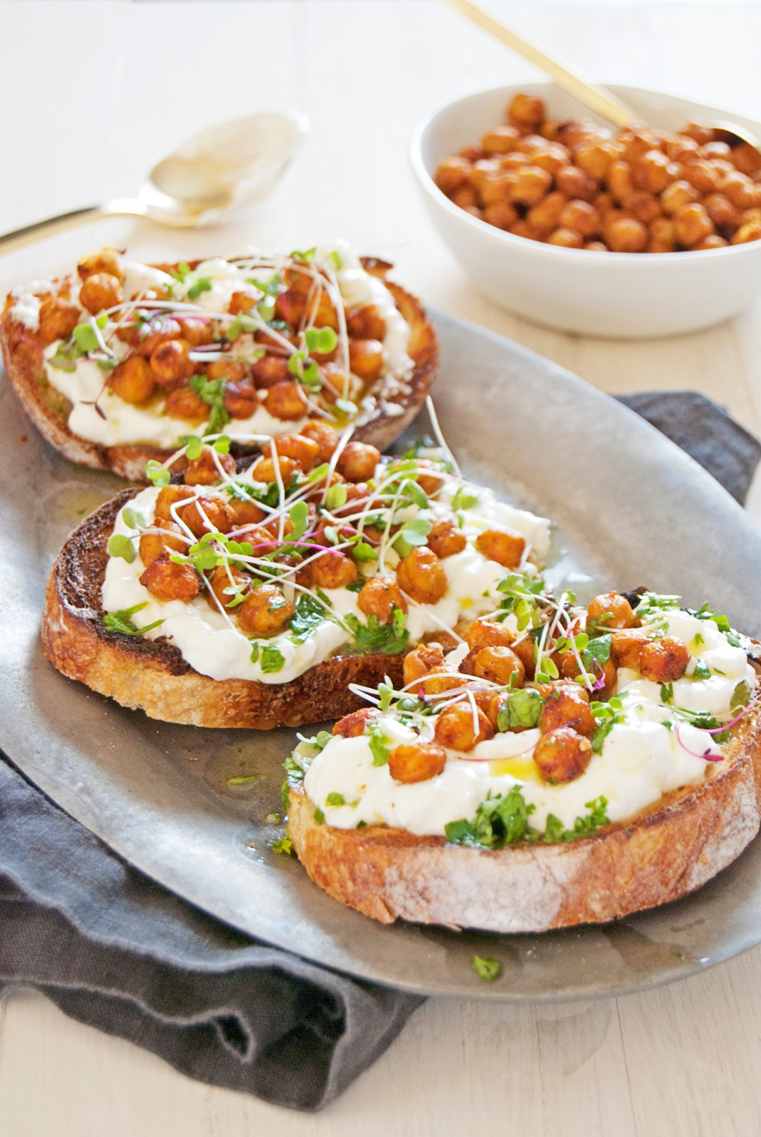 These tasty crostini feature crispy chickpea topping with Greek yogurt feta spread and a lemon and herb vinaigrette over crusty bread!