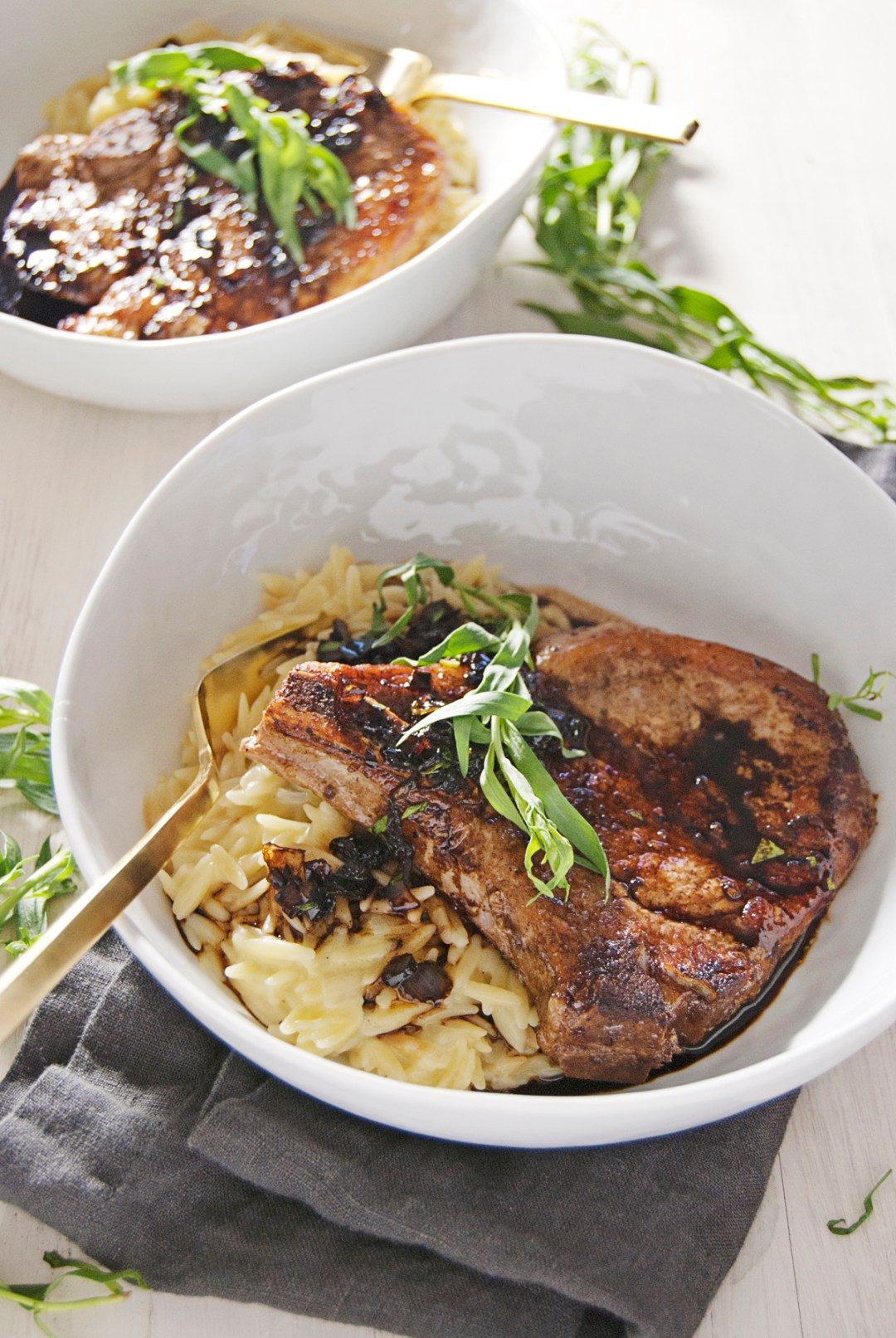 These seared pork chops are heavenly when paired with tangy balsamic glaze, fresh tarragon, and cheesy orzo.