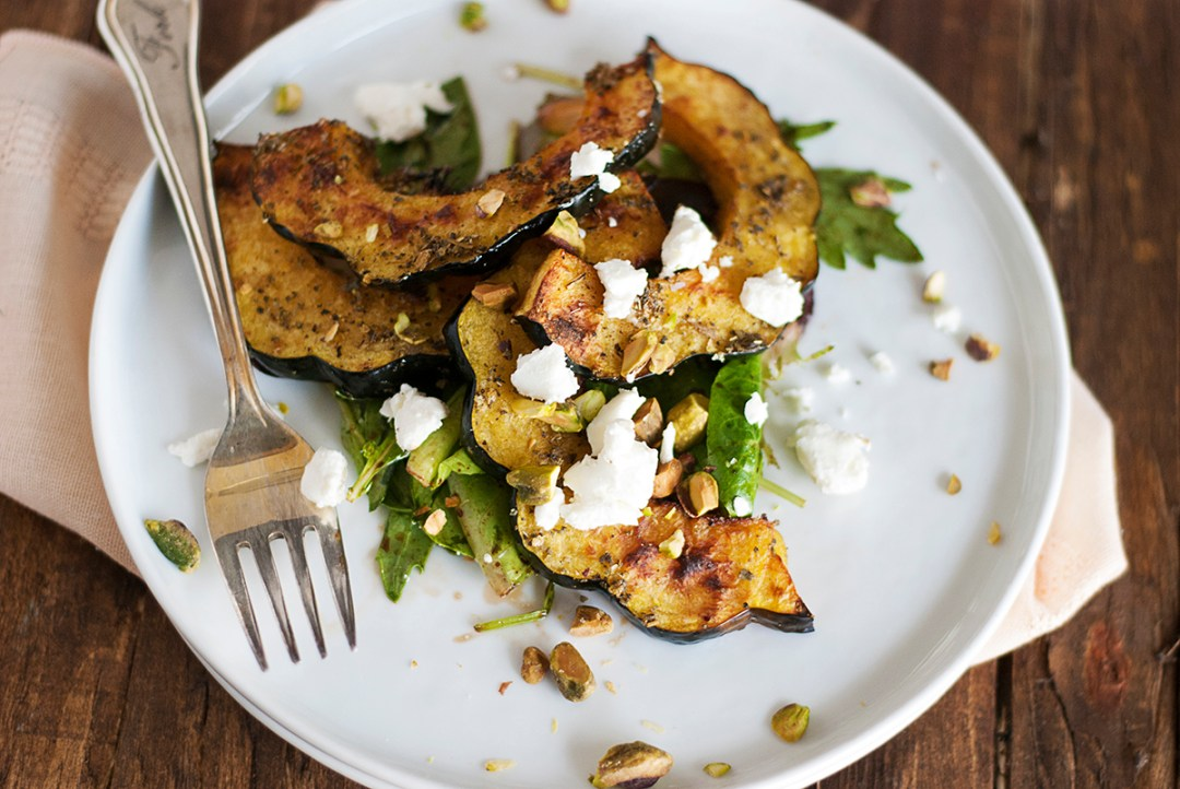This roasted acorn squash salad features tasty winter squash paired with greens, creamy goat cheese, pistachio nuts, and a balsamic vinaigrette.