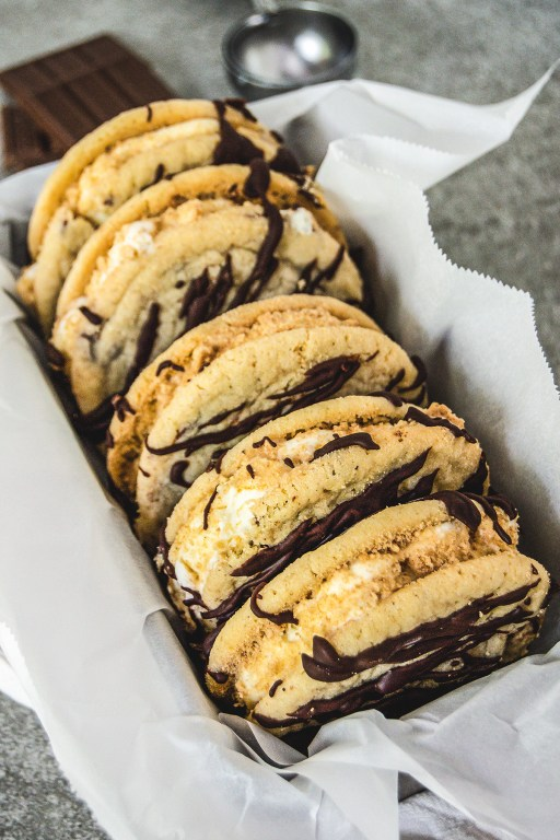 S'mores ice cream sandwiches are the perfect summer treat! Marshmallow ice cream meets chocolate chip cookies with graham cracker coating and a chocolate drizzle!