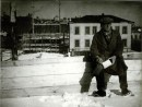 Le Corbusier sitting in front of the construction site for the Tsentrosoiuz Building in Moscow (March 1931)