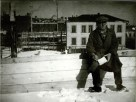 Le Corbusier sitting in front of the construction site for the Tsentrosoiuz building (March 1931)