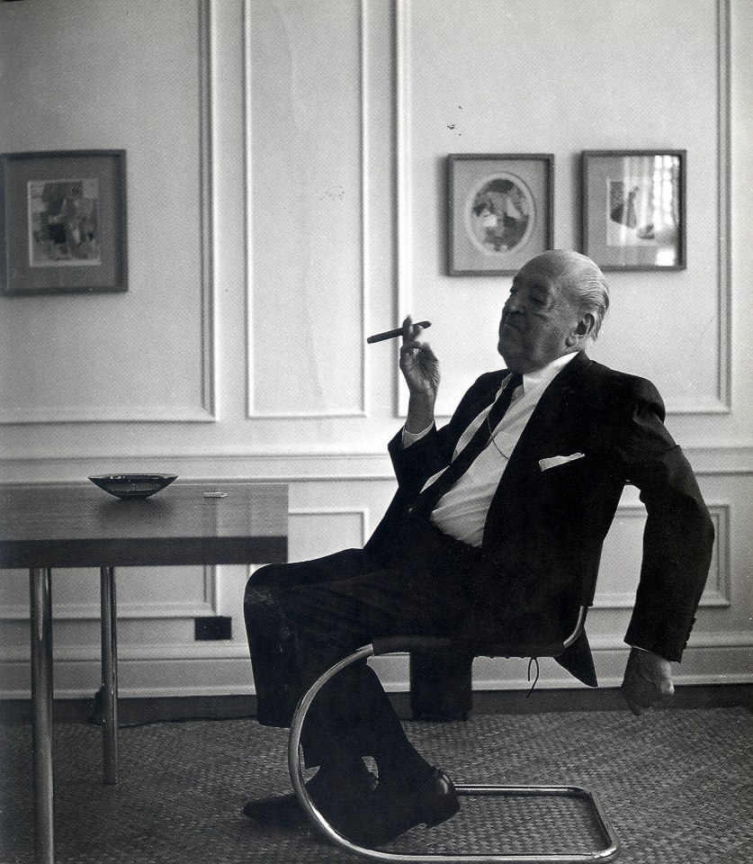 Mies van der Rohe smoking a cigar, sitting on one of his tubular chairs