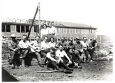 Workers and foreign architects posing for a group photograph during construction of a barrack. Niegeman's wife Gerda is seated amongst the guitar players.