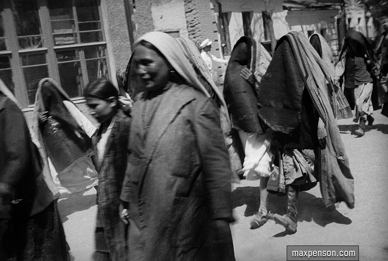 Group of women in yashmaks in the street and two uncovered women. Old Tashkent