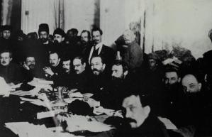 Bukharin (hands clasped) and Lenin (far right), at the Presidium of the Ninth Communist Party Congress in 1920, Mikhail Tomskii seated to B's left, Lev Kamenev (with glasses) at center, and Rykov in forefront