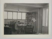 Gruntal, V.G. Interior view of Moisei Ginzburg's studio in the People's Commissariat for Finance (Narkomfin) Apartment Building showing a woman seated at a desk, 25 Novinskii Boulevard, Moscow after 1930