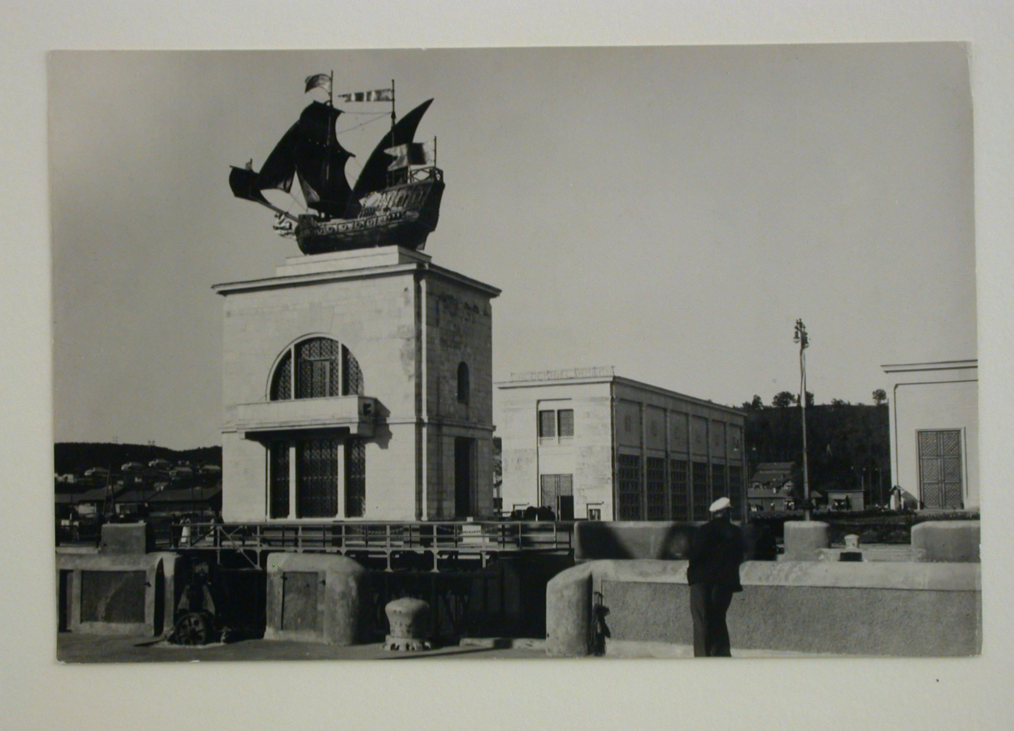 Meyer, Hannes Exterior view of the Moscow-Volga Canal Pumping-station with a modern building surmounted by a replica of a sailing ship in the foreground, Moscow, 1937-1954