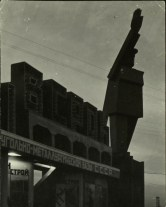Margaret Bourke-White, Silhouette at twilight of gigantic sculptured rendition of a Russian robot w. hand raised in a salute next to unident (Magnitogorsk, 1931)