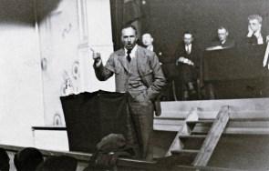 Hendrik de Man op het spreekgestoelte voor het podium tijdens een meeting voor het Plan van de Arbeid in het feestpalies in Kortrijk. Jaren 1930