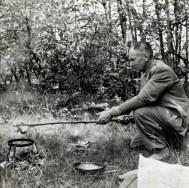 Zwart-witfoto van Hendrik de Man bij het bereiden van de vers gevangen vis boven een open vuurtje in het bos. Jaren 1940