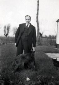 Zwart-witfoto van Hendrik de Man in de tuin met een hond. Jaren 1930