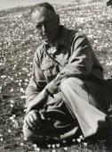 Zwart-witfoto van Hendrik de Man op zijn hukje tussen de bloemen in de Haute Savoie in Frankrijk, 1943