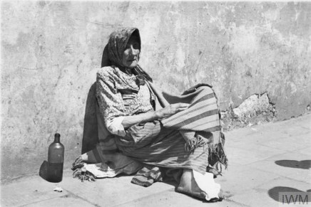 A destitute elderly woman begging in the street