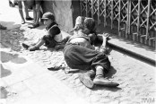 A starving man (father ?) and two emaciated children begging on the street in the ghetto