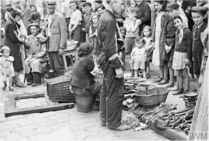 Jewish residents of the ghetto shopping in a vegetable street market
