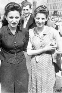 Two well dressed women, most likely sisters, posing for a photograph in a street market