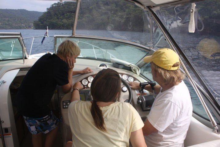 Three people looking at controls on boat