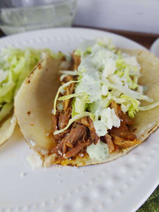 Irish Tacos are the perfect St. Patty's Day dinner! Guinness braised pork topped with cabbage, green crema and queso fresco. The Cheerful Kitchen