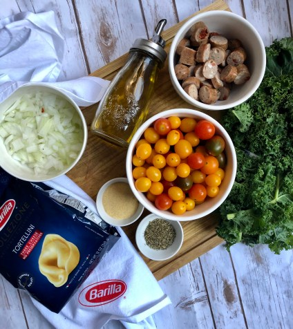 Barilla® Collezione 3 Cheese Tortellini ingredients to make an easy weeknight meal with tomatoes, kale and chicken sausage. Just like a restaurant style dinner!