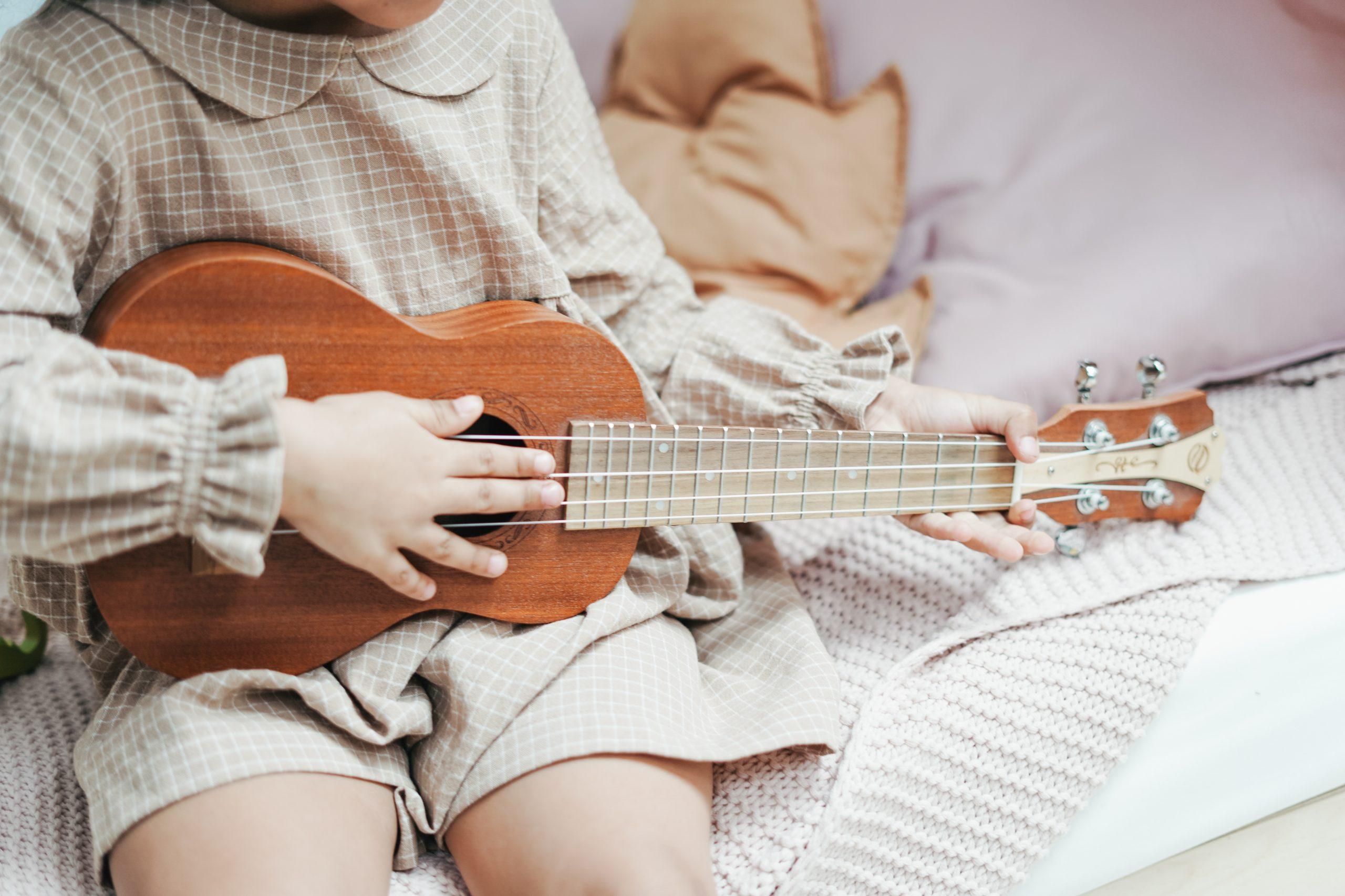girl sitting on bed playing ukulele