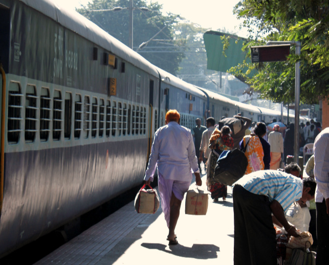 Train on left as people stand on the platform on the right. In the centre a man carries bags.