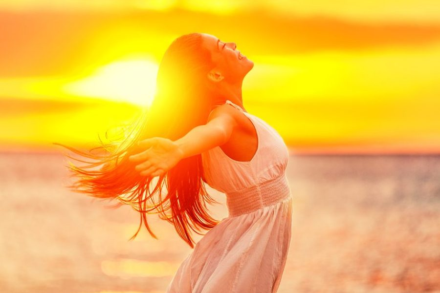 Happy woman feeling free with open arms in sunshine at beach sunset. Freedom and carefree enjoyment girl enjoying life. Beautiful woman in white dress for success, health, hope and faith concept.