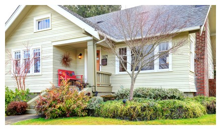 picture of cute home with great landscaping and red bench on front porch