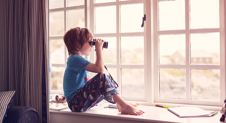 Photo A young boy in his pajamas, sat on a window seat while looking