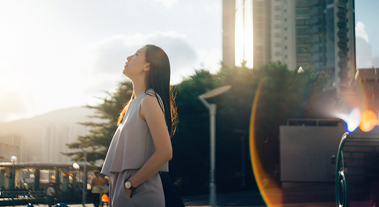 Photo. Young Asian woman looking up to sky in deep thought in the city at sunset