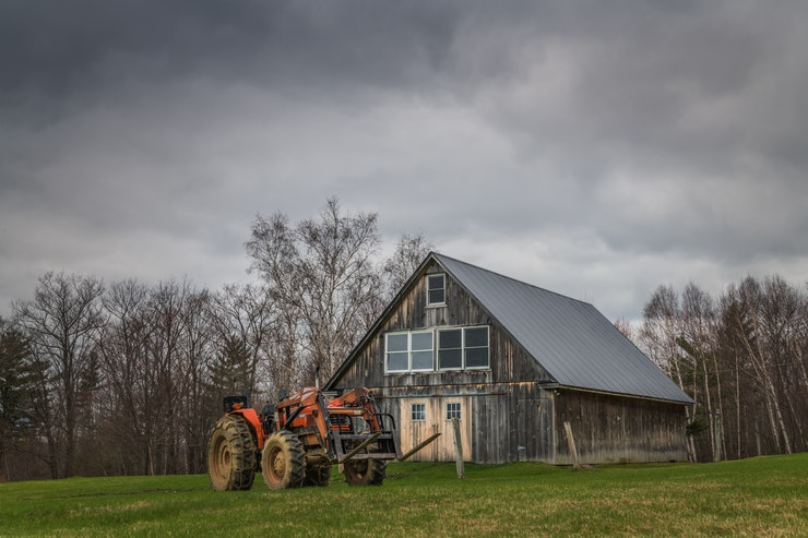 Photo of tractor in front of barn