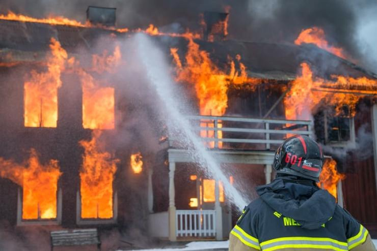 photo of fireman fighting house fire