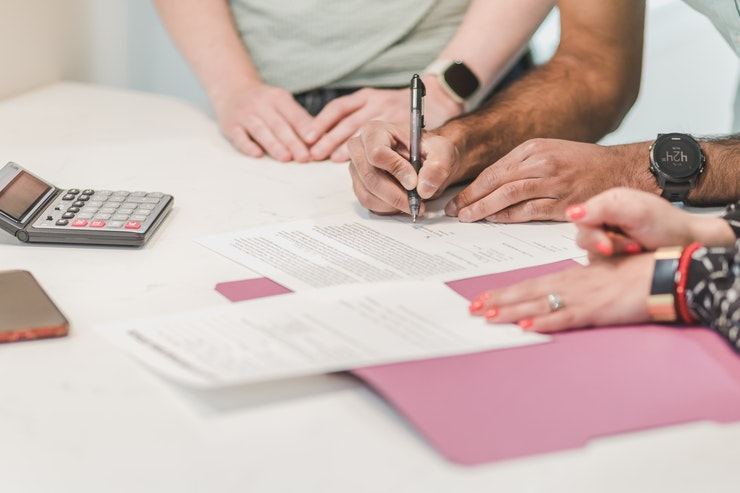 Photo of people signing paperwork