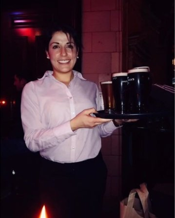 Bianca Machado. Waitress on her workplace serving beer to customers.