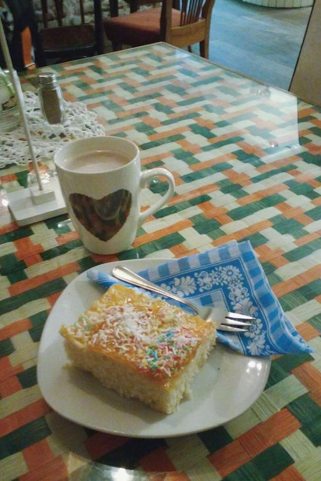 Hot chocolate in a mug with a heart on and pinapple cake with sprinkles on top