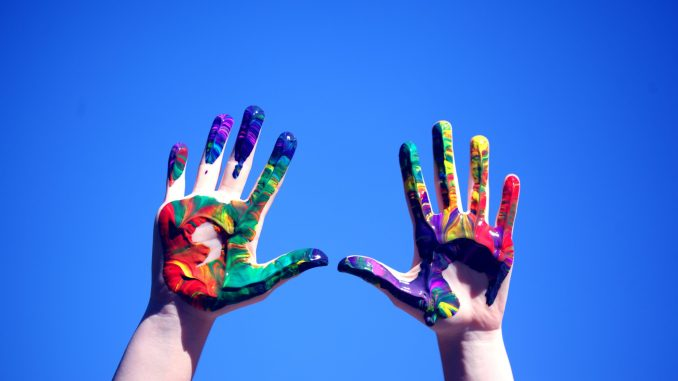Hands against a blue sky, covered with colorful paint