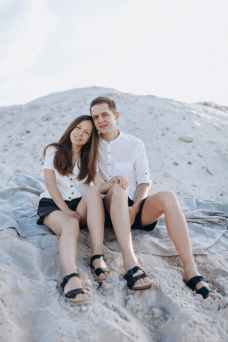 glad couple resting on sandy hill during summer trip