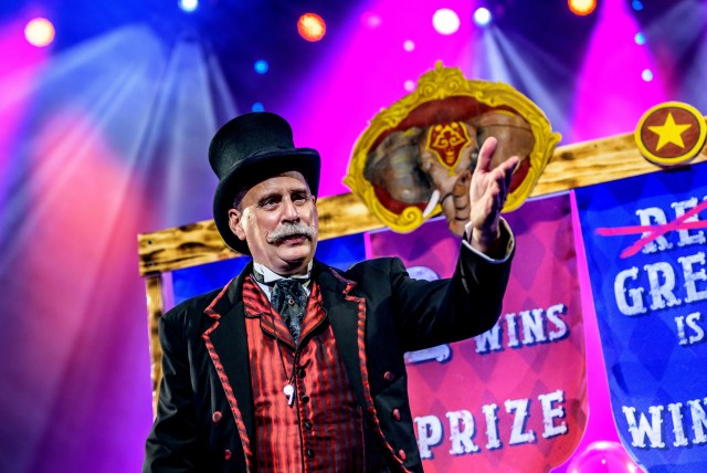 Photo. A man with a bushy grey moustache, a black top hat and tailcoat and striped satin waistcoat holds his hand towards the camera in a welcoming gesture. The background is bright purple and pink with spots and shafts of light. A gold rimmed image of an elephant decorates a banner announcing prizes