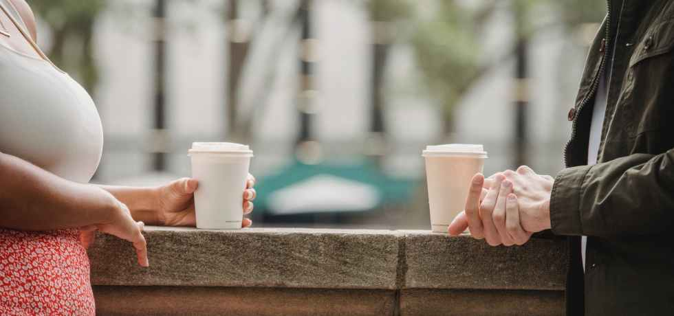 faceless young couple drinking takeaway coffee on terrace