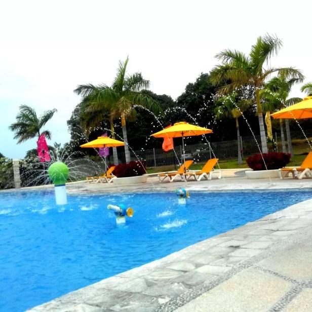 Splash Pool with umbrella and reclining chairs at Aquaria Beach Resort