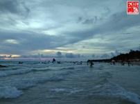 People enjoying the sea as it gets dark