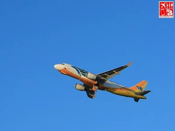 A Cebu Pacific plane flies above us