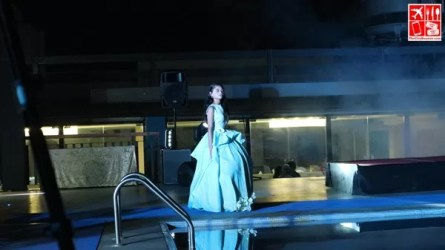 a cosplayer struts her stuff by the pool