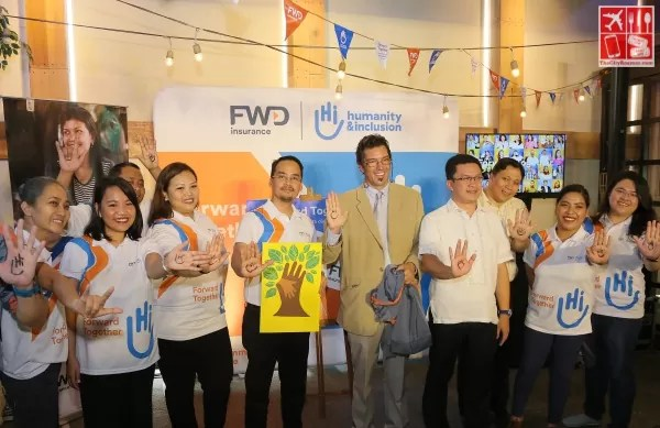 FWD Insurance Community Care volunteers hold up their hands with the stylized Hi for Humanity and Inclusion