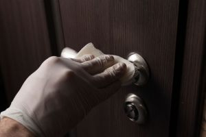 Close-up of disinfection, cleaning and washing of door handles in white gloves.
