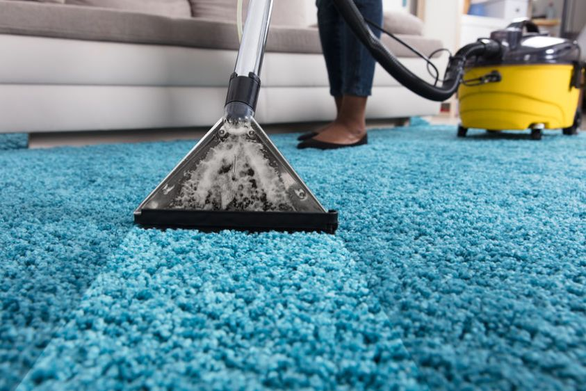 Person Using Vacuum Cleaner For Cleaning Blue Carpet At Home